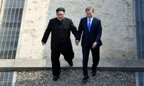 North Korean leader Kim Jong Un, left, and South Korean President Moon Jae-in cross the border line at the border village of Panmunjom in Demilitarized Zone Friday, April 27, 2018. Their discussions will be expected to focus on whether the North can be persuaded to give up its nuclear bombs. (Korea Summit Press Pool via AP)